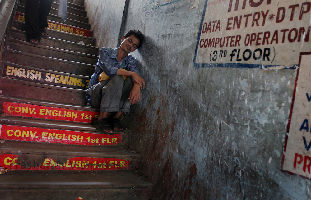 A man sleeps in the stairway of a building housing many of the English Speaking Classes adjacent to the Dadar station, in Mumbai, India, on Monday August 20, 2007. Photographer:  Prashanth Vishwanathan