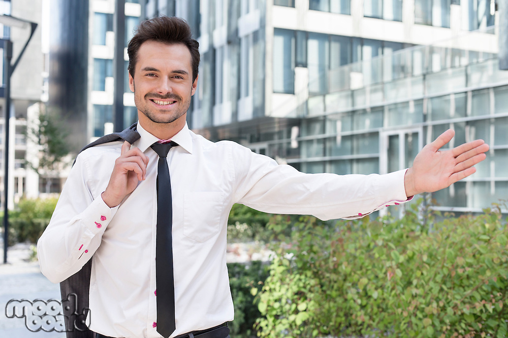 Portrait of happy businessman gesturing while standing outside office building