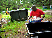 Sapelo Island resident Maurice Bailey deposes of trash at the dump at on Sapelo Island, Ga. State of Georgia Department of Natural Resources employees and residents must maintain the site. Property owners are facing higher taxes, and fees from the county threatening an already fragile Geechee-Gullah community of Hog Hammock. (Stephen Morton for The New York Times)