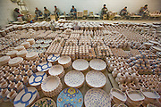 "Painters apply color to bisqueware at Morvarid (Pearl) pottery Factory, Meybod (Also spelled ""Maybod""), Iran. Each of the painters applies an assigned traditional design."