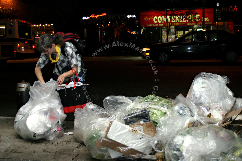 Janet, 43, one of the founders of the Freegan community in New York, looking for some edible food in the rubbish during a trash tour along groceries on 3rd Avenue in Manhattan, New York, NY., on Wednesday, June 21, 2006. Freegans are a community of people who aims at recovering wasted food, books, clothing, office supplies and other items from the refuse of retail stores, frequently discarded in brand new condition. They recover goods not for profit, but to serve their own immediate needs and to share freely with others. According to a study by a USDA-commissioned study by Dr. Timothy Jones at the University of Arizona, half of all food in the United States is wasted at a cost of $100 billion dollars every year. Yet 4.4 million people in the United States alone are classified by the USDA as hungry. Global estimates place the annual rate of starvation deaths at well over 8 million. The massive waste generated in the process fills landfills and consumes land as new landfills are built. This waste stream also pollutes the environment, damages public health as landfills chemicals leak into the ground, and incinerators spew heavy metals back into the atmosphere. Freegans practice strategies for everyday living based on sharing resources, minimizing the detrimental impact of our consumption, and reducing and recovering waste and independence from the profit-driven economy. They are dismayed by the social and ecological costs of an economic model where only profit is valued, at the expense of the environment. In a society that worships competition and self-interest, Freegans advocate living ethical, free, and happy lives centred around community and the notion that a healthy society must function on interdependence. Freegans also believe that people have a right and responsibility to take back control of their time.