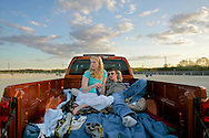 "Stephanie Malloy and Tom Nowak of Evergreen Park relax in a truck bed and listen to the Cubs game on the radio before the start of the movie ""The Benchwarmers"" at the Cascade Drive-In in West Chicago."