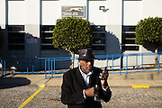 "MONTGOMERY, AL – JANUARY 25, 2016: Michael Harris, 52, receives a call from a regular client while waiting for customers at the new Greyhound station on South Boulevard. In 2011, the downtown Montgomery Greyhound bus station was converted into a museum to honor the freedom riders, who endured a violent attack there in 1961. The replacement bus station, located four miles from downtown, is a prime business opportunity for independent cabbies like Michael Harris, who make a living serving passengers unwilling to rely on city buses. Many characterize the public bus system in Montgomery as unsafe and unreliable, so wary passengers cough up $2 per mile for trips in Mr. Harris' 2005 Lincoln Navigator, traveling across town for fast food, or sometimes as far as New York City. ""This is my life,"" Harris said. ""I love driving, and I help people out. It's just in my heart."""