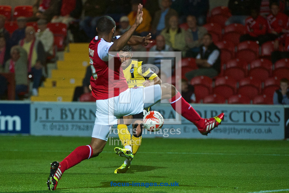 Dale Jennings of Barnsley shoots at goal under pressure from Nathan Pond of Fleetwood Town during the Sky Bet League 1 match at the Highbury Stadium, Fleetwood<br /> Picture by Ian Wadkins/Focus Images Ltd +44 7877 568959<br /> 17/09/2014