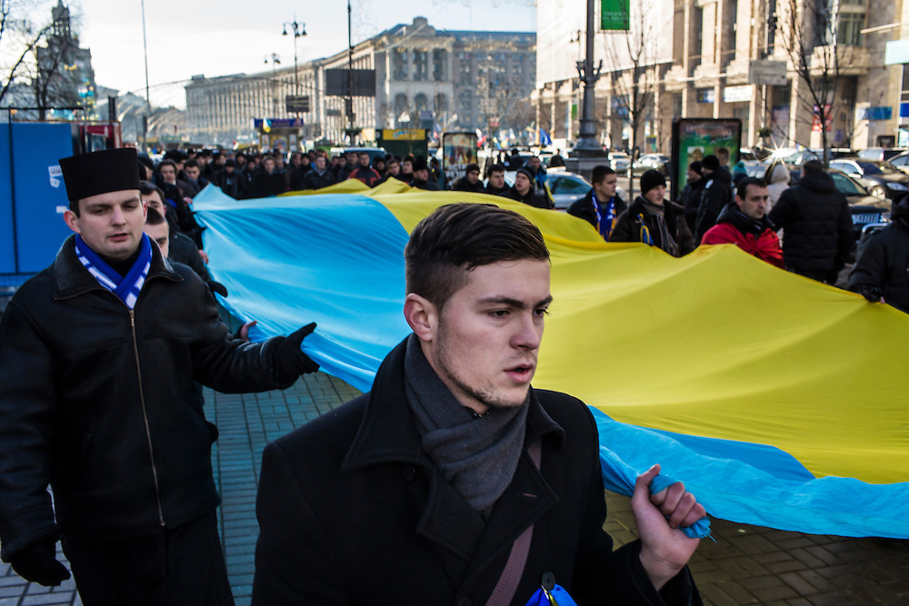 KIEV, UKRAINE - DECEMBER 4: Anti-government protesters carry a large Ukrainian flag through the streets on December 4, 2013 in Kiev, Ukraine. (Photo by Brendan Hoffman/Getty Images)