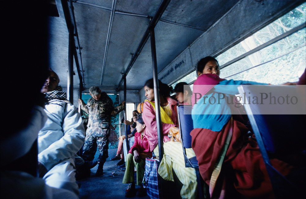Kathmandu Valley, 12 February, 2005. Military check point on the outskirt of Kathmandu.  All the men get off the bus and walk through the checkpoint, women and foreigners are allowed to stay in the bus. A soldier checks the luggages on board.