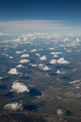 Aerial photograph with nice puffy white clouds above farmland.
