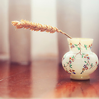 Close up of a decorated small pitcher with a stick of wheat inside.