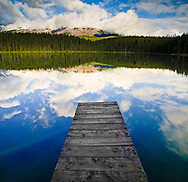 A dock juts out into Leach Lake in Jasper National Park as the morning sky is reflected in the still water.