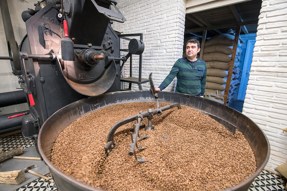 Adult male leans against coffee bean roaster as a mechanical arm slowly rotates freshly roasted coffee beans to cool them down, Istanbul, Turkey.