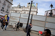 "A pigeon takes off from approaching pedestrians next to a temporary construction hoarding beneath the partially hidden statue of the world famous London Victorian-era landmark, Eros in Piccadilly Circus, on 25th February 2020, in London, England. Eros, or the Shaftesbury Memorial Fountain is located at the southeastern side of Piccadilly Circus in London, United Kingdom. Moved after World War II from its original position in the centre, it was erected in 1892–1893 to commemorate the philanthropic works of Lord Shaftesbury, who was a famous Victorian politician and philanthropist. The monument is surmounted by Alfred Gilbert's winged nude statue generally, though mistakenly, known as Eros. This has been called ""London's most famous work of sculpture."""