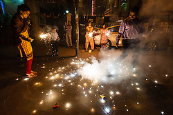 © Licensed to London News Pictures. 13/11/2012. Delhi, India. A family jump excitedly around fireworks outside their home during the first night of Diwali, known as Dhanteras.  Photo credit : Richard Isaac/LNP