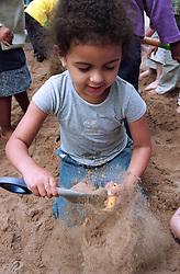 Nursery school girl throwing sand around in playground sandpit,
