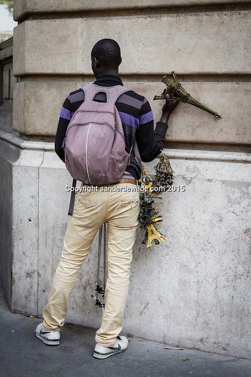 story on  men of African origins illegaly in Europe sells souvenirs to tourist close to the Eiffel tower in Paris. Here he hides for the police at a wall, hiding his miniature Eiffel towers and selfie sticks for the passing pollice cars.Stock in his back pack.