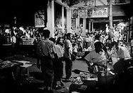 Sidewalks packed with pedestrians, food vendors, and tea shops in the evening, Yangon, Burma.