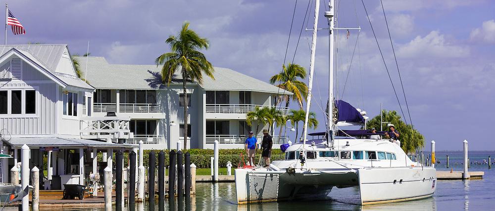 Vacationers sailing luxury catamaran yacht into port at upmarket South Seas Island Resort, Captiva Island in Florida, USA