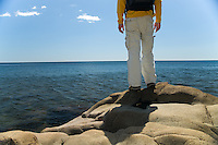 Hiker standing on the shores of Lake Superior enjoying the blue sky and blue water of Minnesota's north shore.