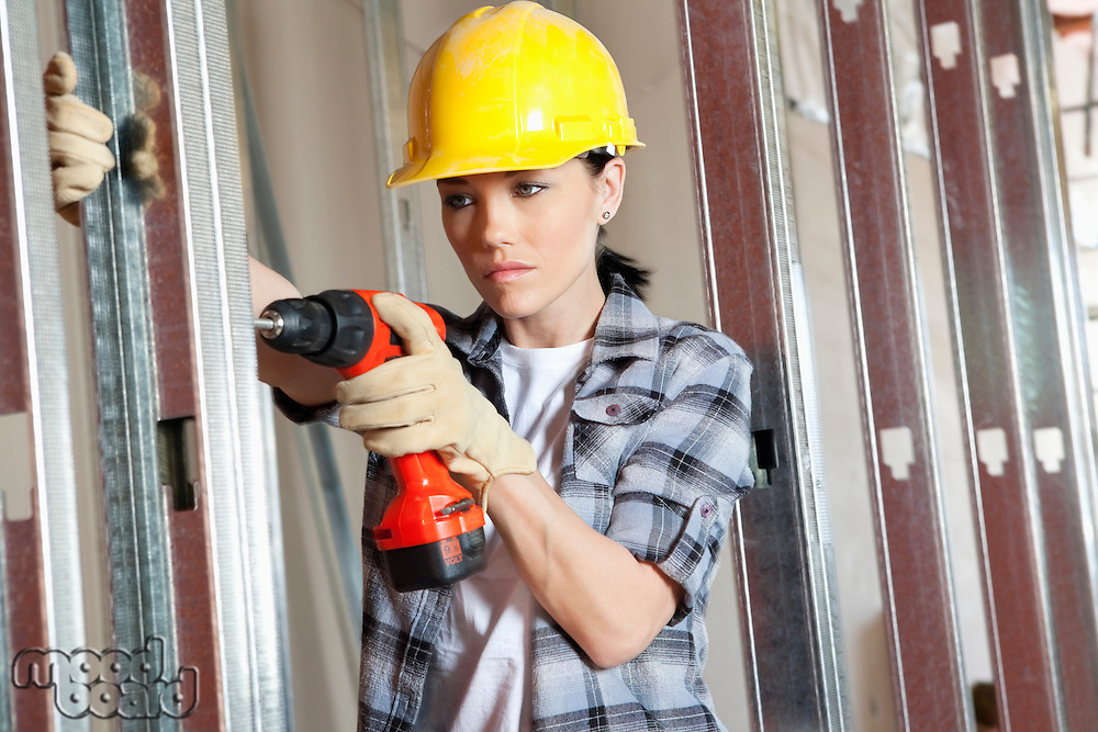 Mid adult female contractor drilling at construction site