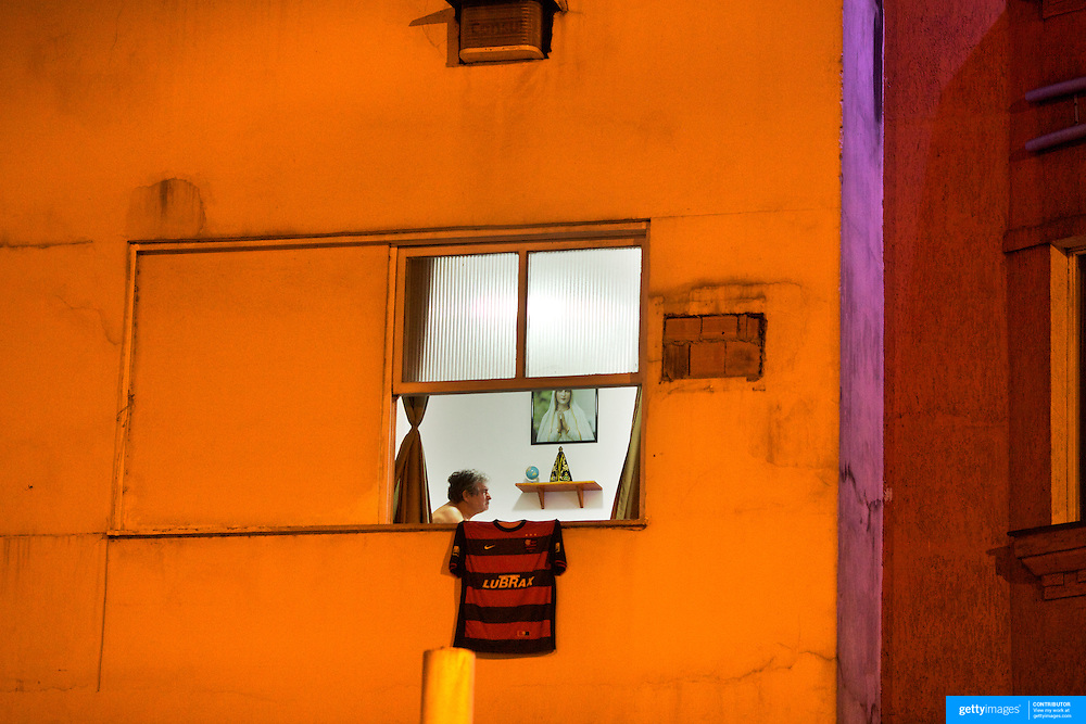 A Flamengo fan watches the football on the television in his apartment as his Flamengo shirt hangs out of his apartment window in Copacabana, Rio de Janeiro,  Brazil. 1st October 2010. Photo Tim Clayton