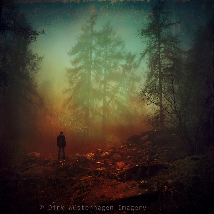 Man standing a the end f a path facing trees looming above in the fog and rain.<br />