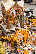 26 MARCH 2010 - BANGKOK, THAILAND:  People lay flower garlands on the Erawan Shrine in Bangkok. The Erawan Shrine (Thai: San Phra Phrom) is a Hindu shrine in Bangkok, Thailand that houses a statue of Phra Phrom, the Thai representation of the Hindu creation god Brahma. The Erawan Shrine was built in 1956 as part of the government-owned Erawan Hotel to eliminate the bad karma believed caused by laying the foundations on the wrong date. The hotel's construction was delayed by a series of mishaps, including cost overruns, injuries to laborers, and the loss of a shipload of Italian marble intended for the building. Furthermore, the Ratchaprasong Intersection had once been used to put criminals on public display. An astrologer advised building the shrine to counter the negative influences. The Brahma statue was designed and built by the Department of Fine Arts and enshrined on 9 November 1956. The hotel's construction thereafter proceeded without further incident.      PHOTO BY JACK KURTZ