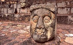 Carved head and archeological ruins in Honduras.
