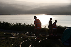 "© Licensed to London News Pictures . 28/06/2018 . Saddleworth , UK . Firefighters pumping water at Higher Swineshaw Reservoir . The army are being called in to support fire-fighters , who continue to work to contain large wildfires spreading across Saddleworth Moor and affecting people across Manchester and surrounding towns . Very high temperatures , winds and dry peat are hampering efforts to contain the fire , described as "" unprecedented "" by police and reported to be the largest in living memory . Photo credit: Joel Goodman/LNP"