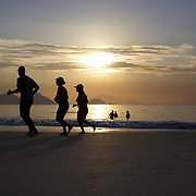 Early morning walkers and swimmers at sunrise on Copacabana beach, Rio de Janeiro,  Brazil. 9th July 2010. Photo Tim Clayton..The beaches of Rio de Janeiro, provide the ultimate playground for locals and tourists alike. Beach activity is in abundance as beach volley ball, football and a hybrid of the two, foot volley, are played day and night along the length and breadth of Rio's beaches. .Volleyball nets and football posts stretch along the cities coastline and are a hive of activity particularly at it's most famous beaches Copacabana and Ipanema. .The warm waters of the Atlantic Ocean provide the ideal conditions for a variety of water sports. Walkways along the edge of the beaches along with exercise stations and cycleways encourage sporting activity, even an outdoor gym is available at the Parque Do Arpoador overlooking the ocean. .On Sunday's the main roads along the beaches of Copacabana, Leblon and Ipanema are closed to traffic bringing out thousands of people of all ages to walk, run, jog, ride, skateboard and cycle more than 10 km of beachside roadway. .This sports mad city is about to become a worldwide sporting focus as they play host to the world's biggest sporting events with Brazil hosting the next Fifa World Cup in 2014 and Rio de Janeiro hosting the Olympic Games in 2016..