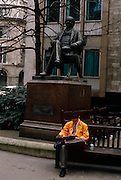 A trader from the LIFFE futures exchange takes a break in the street during a weekday lunchtime, beneath the statue of George Peabody in the City of London. Wearing the orange jacket of this once thriving financial instutution, we see a scene of wealth and prosperity, from an era of growth during the industrial revolution to the arrogance and self-indulgence during the government of John Major - a political inheritance from Margaret Thatcher. Peabody was a philathropist, banker and entrepreneur ( 1795 - 1869).