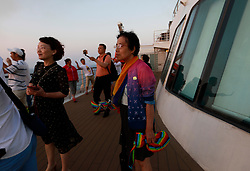 Parents of Chinese LGBTs (lesbian, gay, bisexual and transgender) and volunteers of the Parents and Friends of Lesbians and Gays (PFLAG) China organisation stand on the deck with rainbow coloured scarfs on a cruise in open seas on route back to Shanghai, China, 17 June 2017. About 800 members of the Chinese LGBT (lesbian, gay, bisexual and transgender) community and their parents spent four days on a cruise trip organised by Parents and Friends of Lesbians and Gays (PFLAG) China, a grassroots non-government organisation, celebrating the 10th anniversary of the organisation. It aims to promote coexistence among homosexuals and their families.