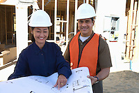 Architect and construction worker looking at blueprints on construction site