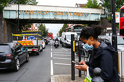 © Licensed to London News Pictures. 30/06/2020. London, UK. A woman wearing a face covering crosses the road under the railway bridge on Green Lane, Harringay. London Borough of Haringey in north London is amongst 36 areas in England where COVID-19 cases are rising according to Public Health England. Photo credit: Dinendra Haria/LNP
