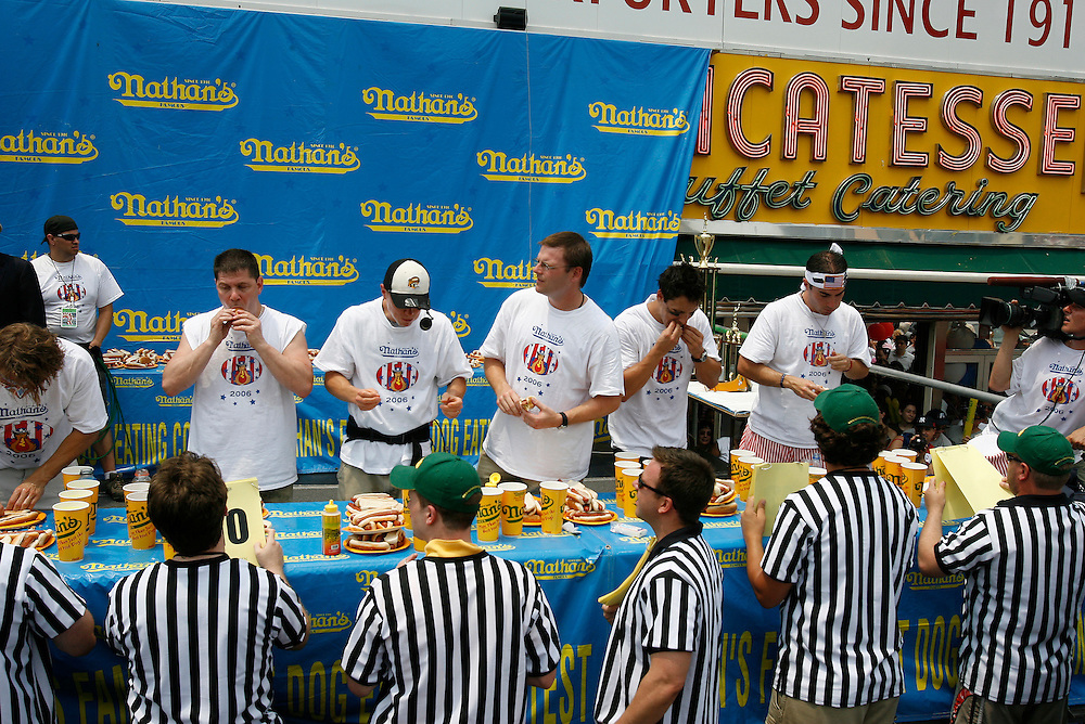 NEW YORK, NY-06 JUL04-- Competitors chow down during the hot dog eating competition under the watchful eyes of referees. (Extra) The Gazette/Liam Maloney