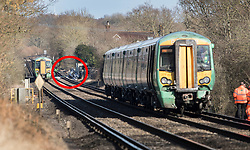 © Licensed to London News Pictures. 17/02/2018. Horsham, UK. The remains of a car (circled in red) is seen further up the track near the level crossing where the southbound train (seen at right with damage to the lower front)  remains stationary after two people were killed near the village of Barns Green. Photo credit: Peter Macdiarmid/LNP