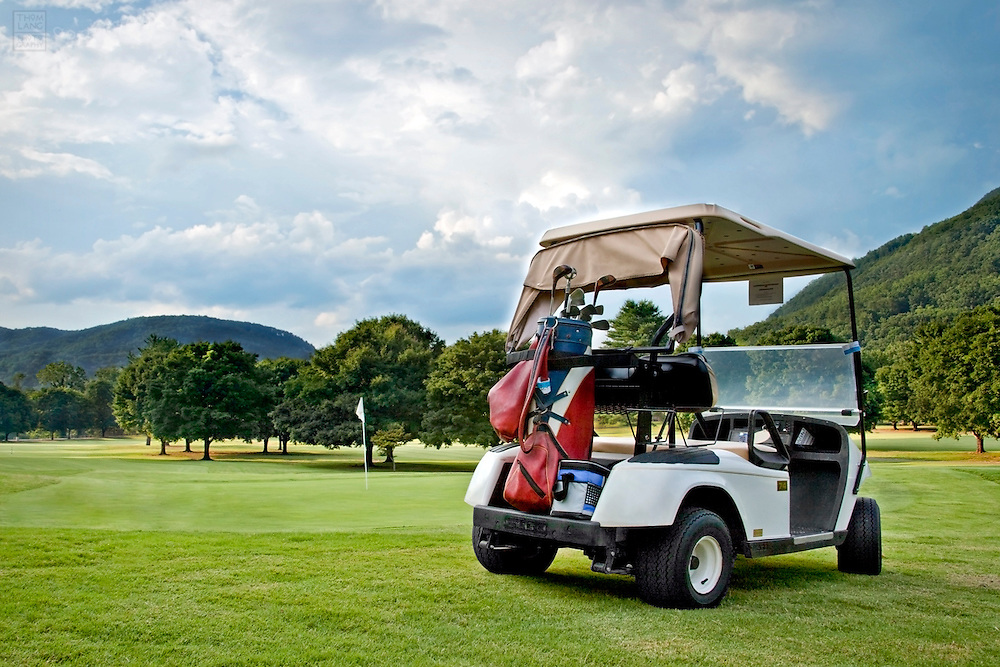 A retro golf cart sits parked alone on a golf course.