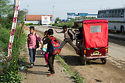 18th March 2014, Shakarpur, New Delhi, India. Children disembark from a rickshaw at a makeshift school under a metro bridge near the Yamuna Bank Metro station in Shakarpur, New Delhi, India on the 18th March 2014<br /> <br /> Rajesh Kumar Sharma (born 01/02/1970), started this makeshift school in 2011. Six mornings a week he teaches underprivileged children for three hours while his younger brother replaces him at his general store in Shakarpur. His students are children of labourers, rickshaw-pullers and farm workers. This is the 3rd site he has used to teach under privileged children in the city, he began in 1997. <br /> <br /> PHOTOGRAPH BY AND COPYRIGHT OF SIMON DE TREY-WHITE<br /> + 91 98103 99809<br /> email: simon@simondetreywhite.com<br /> photographer in delhi<br /> journalist
