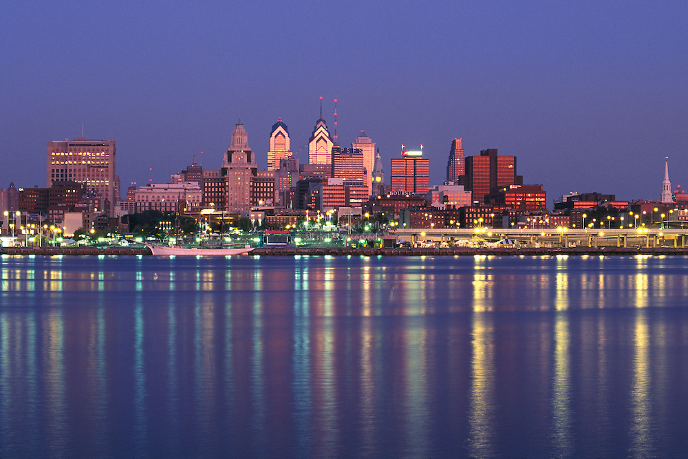 Philadelphia Pennsylvania USA skyline at sunrise with Delaware River in foreground. view from Camden, New Jersey<br />