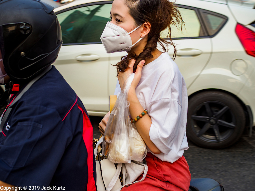 31 JANUARY 2019 - BANGKOK, THAILAND:   A woman wearing a breathing mask because of the air pollution in Bangkok on the back of a motorcycle in central Bangkok. The Thai government has closed more than 400 schools for the rest of the week because of high levels of pollution in Bangkok. At one point Wednesday, Bangkok had the third highest level of air pollution in the world, only Delhi, India and Lahore, Pakistan were worst. The Thai government has suspended some government construction projects and ordered other projects to take dust abatement measures. Bangkok authorities have also sprayed water into the air in especially polluted intersections to control dust. Bangkok's AQI (Air Quality Index) Thursday morning was 180, which is considered unhealthy for all people.     PHOTO BY JACK KURTZ