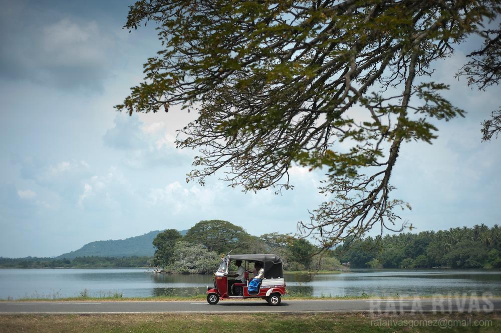 A tuc-tuc drives alongside Tissa Lake, in Tissamaharama, Sri Lanka, on February 27, 2011.