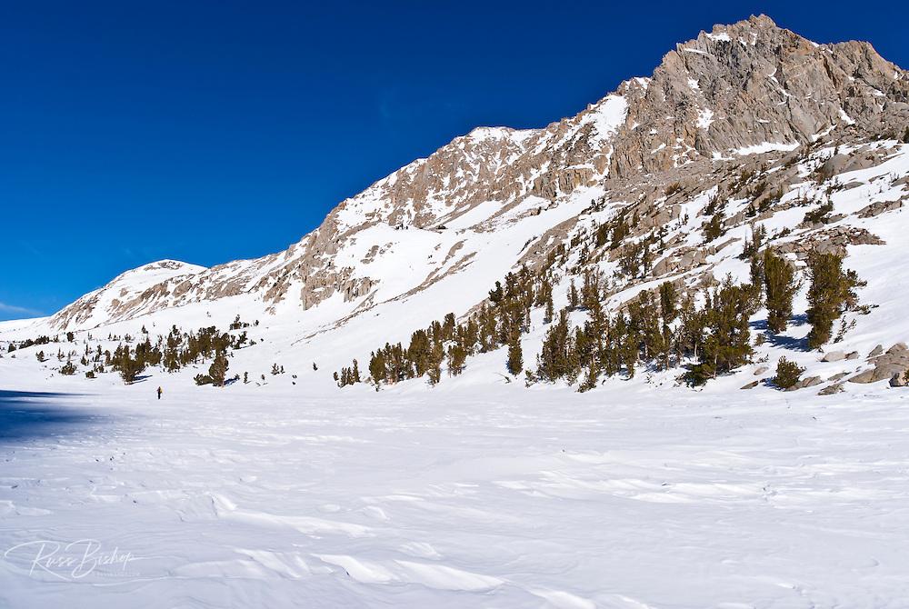 Backcountry skier crossing Loch Leven under Piute Pass, John Muir Wilderness, Sierra Nevada Mountains, California