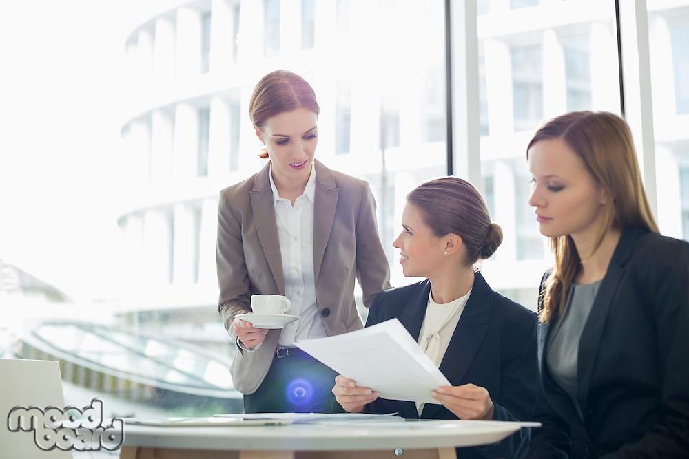 Businesswomen with paperwork during coffee break