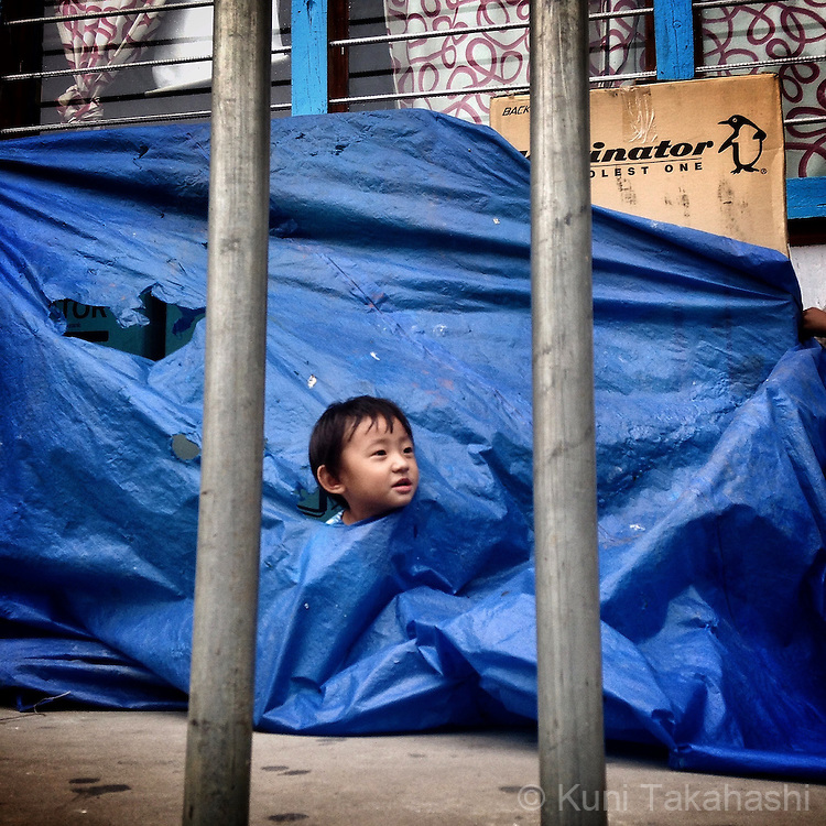 Boy plays under cover at market in Trashigang, Bhutan on Sep 11, 2015. (Photo by Kuni Takahashi)