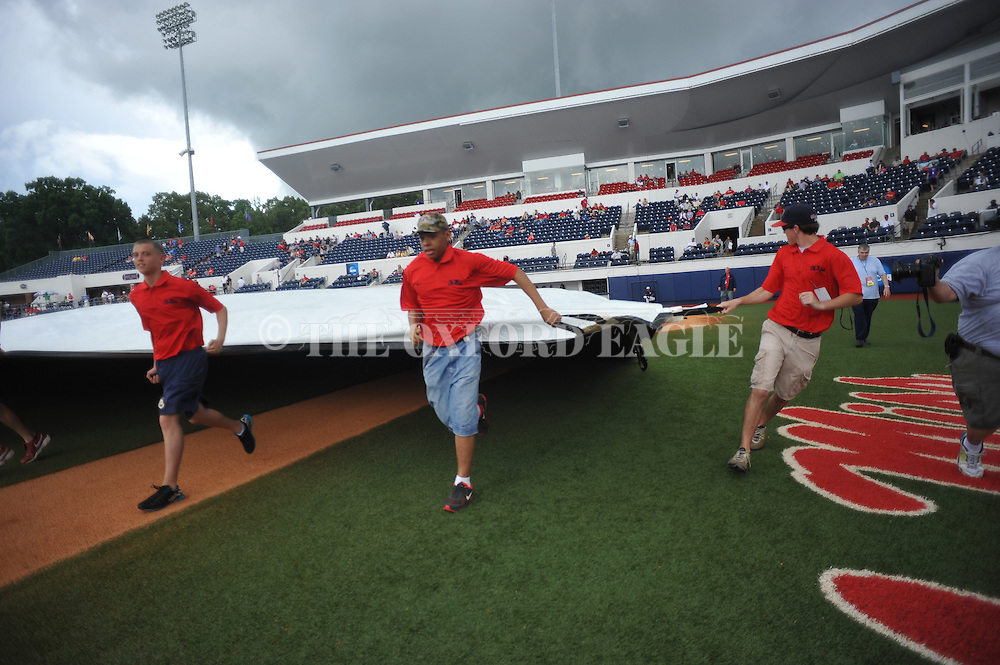 The grounds crew puts the tarp on the field during a rain delay before the Georgia Tech vs. Washington at the NCAA Oxford Regional at Oxford-University Stadium on Friday, May 30, 2014. (AP Photo/Oxford Eagle, Bruce Newman)