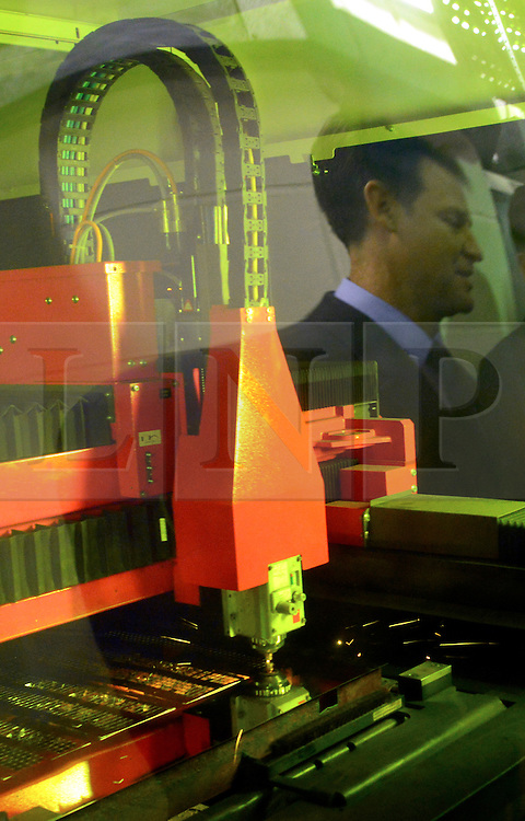 © Licensed to London News Pictures. 19/12/2013. Sutton, UK. NICK CLEGG reflected in the safety screen on a laser cutting machine. . Deputy Prime Minister and Liberal Democrat Leader Nick Clegg and Sutton and Cheam MP Paul Burstow visit Nu-Flame – a successful local company making fireplaces at the heart of the Kimpton Park Business Improvement District (BID). The pair met with workers and managers at the factory to learn about the success of the BID. Photo credit : Stephen Simpson/LNP