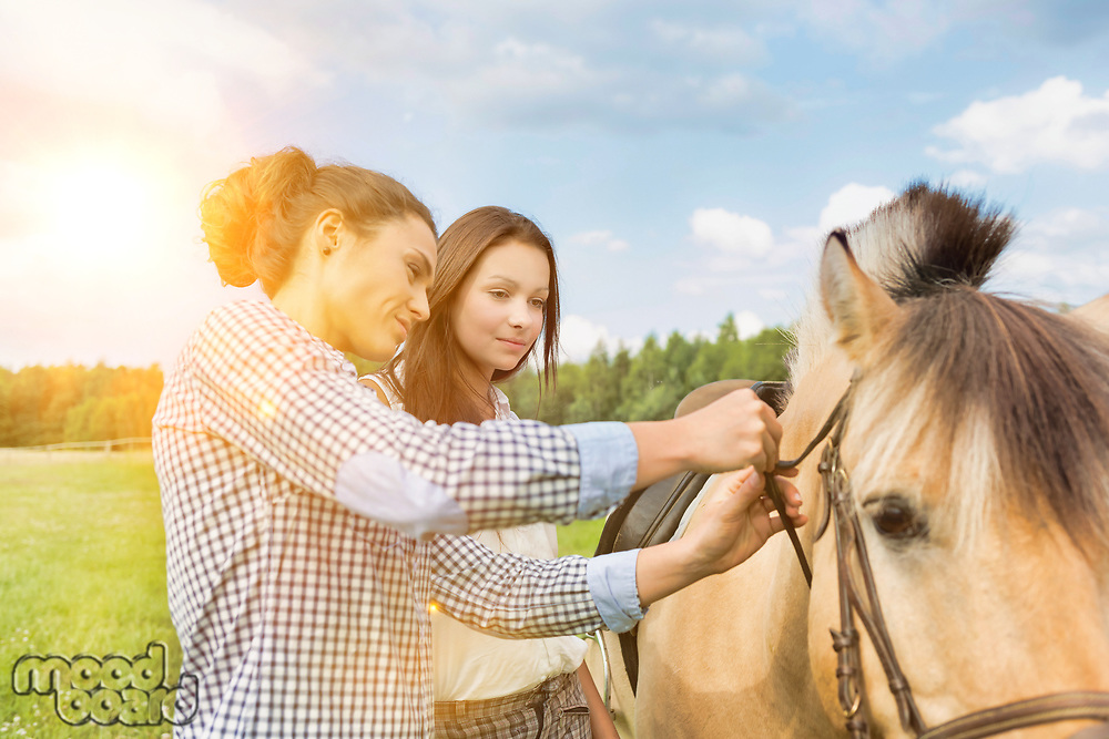 Portrait of mature woman teaching young woman on how to pull horse bit