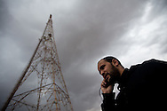 An engineer talks on the phone outside a Free Libya radio station formed after proestors took control of the town and burnt the state radio station in Benghazi on March 1, 2011.