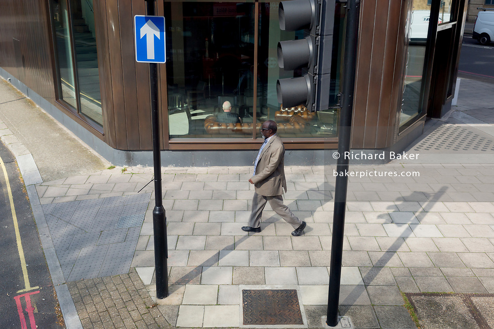 A black man walks through the shadows of street posts in Southwark, on 28th March 2019, in London, England