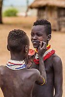 Teenaged Kara tribe girl having her face painted, Omo Valley, Ethiopia.