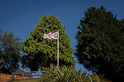 A union jack flies proudly in front of tall Leylandii trees in a garden at Horning on the Norfolk Broads. As a statement of British territorial ownership in sububia where an Englishman's home is his castle is reflected also in his garden and the high boundaries between him and his neighbour, with the blight of the evergreen - a screen of privacy and supremacy. Even on sites of relatively poor culture, plants have been known to grow to heights of 15 metres (49 ft) in 16 years. Their rapid, thick growth means they are sometimes used to enforce privacy, but such use can result in disputes with neighbours whose own property becomes overshadowed.[