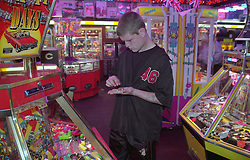 Young homeless man counting money in seaside arcade,